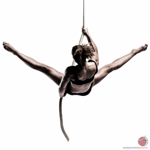 Circus aerialist lowering herself on a rope with legs in side splits