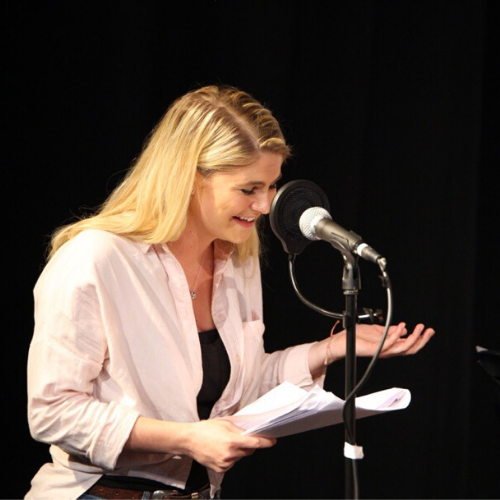 Female actor, holding script, laughs into microphone