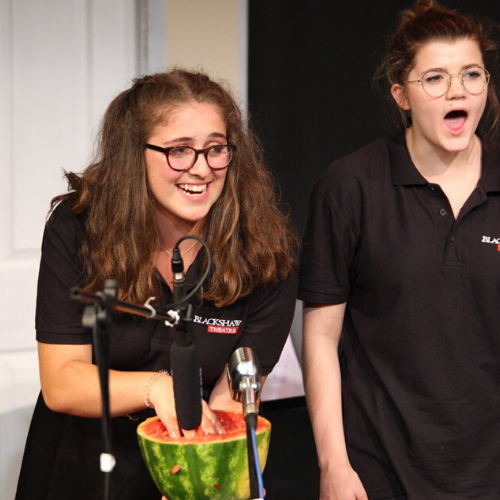 Female foley artist laughs as she digs her hands into a melon to make a sound effect, her female colleague stands next to her, shocked expression on her face.