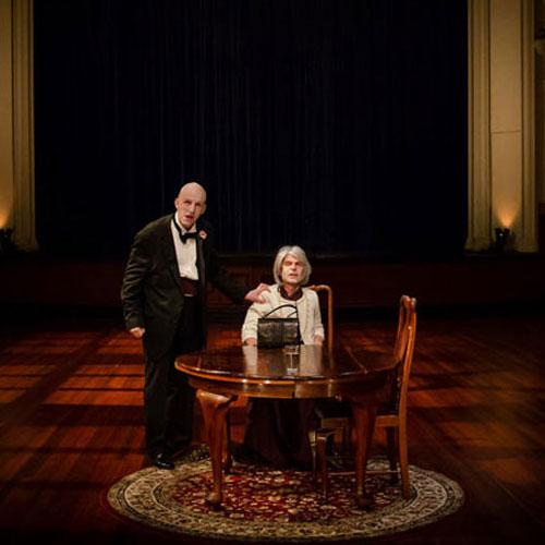 A dark ballroom, a wooden table and patterned rug in centre. A man in a suit and person in a dress sitting besides table.