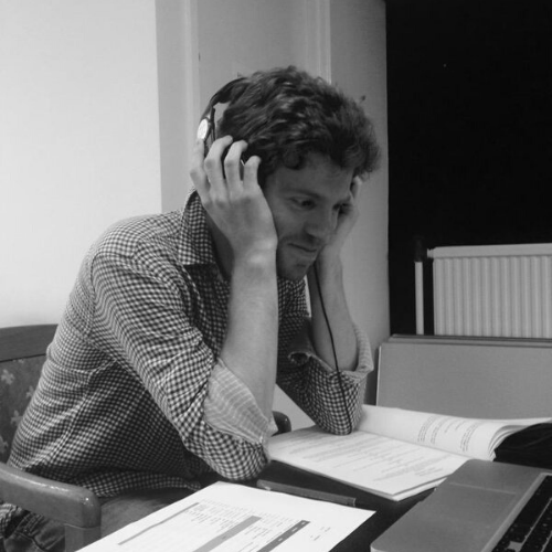 A man listens, excitedly, on his headphones, across his table, script pages are scattered