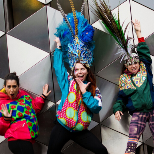 Dancers against a wall in colourful jackets and feather headresses