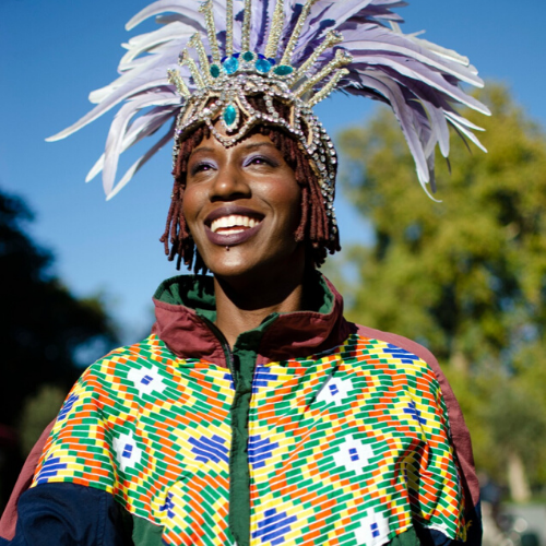 Girl in colourful jacket and feather headress smiling