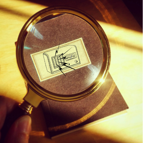 A magnifying glass hovers over a book, magnifying an illustrated image of an old-fashioned radio