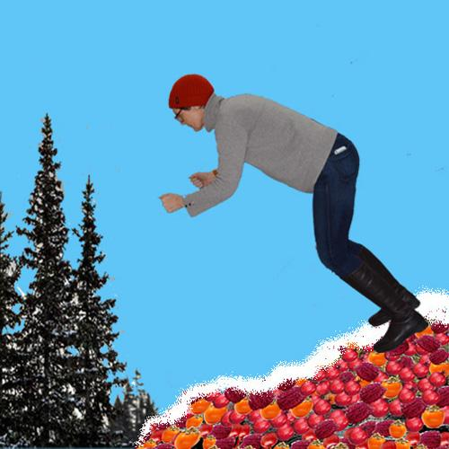Woman in jeans and jumper and red hat skiing - with no skis or poles - down a snowy hill of fruit towards pine trees