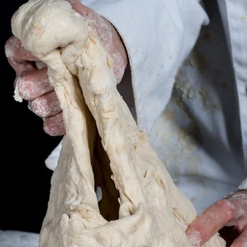 The image is of a lump of uncooked bread dough being stretched into a mouth by two hands which are not fully in shot.