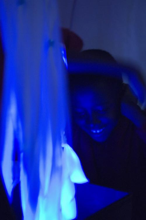 From Oily Cart show Blue. Very blue lighting, a boy's smiling face illuminated by light box he is holding