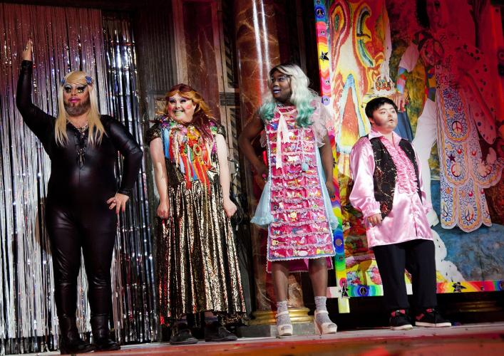 4 Fabulously dressed Drag artists on stage with a colourful backdrop.