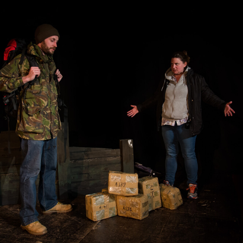 A man (gormless) and woman (frustrated), dressed in outdoor gear, stand by a coastal groyne, and a pile of wrapped drugs.